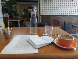 coffee cup, water, writing pad, pen on wooden table in cafe